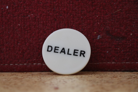 A small token with inscription dealer with black colour