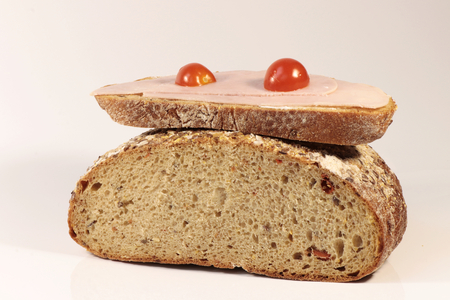 A slice of bread with ham and tomato on half of bread on the white background
