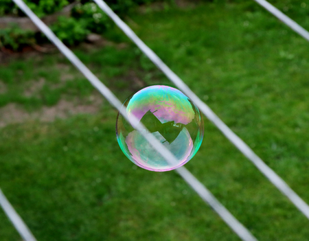 A amazing colourful bubble between two cords and above earth. Flying in the air. Orange, green, purple in circle