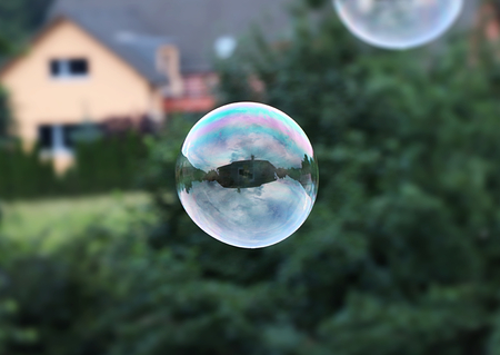 A one big bubble flying in the air. Bubble serve as mirror so we can see some house and cloudy. Bubble is mainly created from green and purple colour. In the backround there are trees and building 스톡 콘텐츠