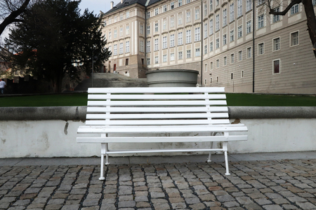 A beautiful historical white bench in around prague castle. Czech republic architecture. Background is a part of prague castle Redactioneel