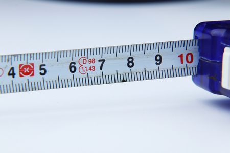 A small tape measure for measuring some length at home or at work on white background