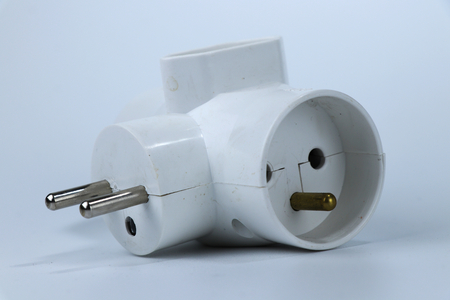 A three way adapter for connect another three cabels to one european socket. White or grey background 写真素材