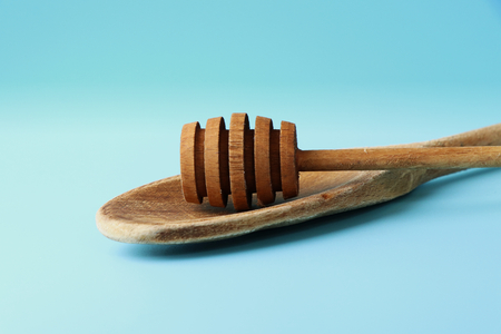 A view on casual wooden spoon on stirring some food and spoon on honey for perfect pick up honey. Blue background