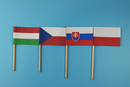 A flags of members visegrad four on wooden sticks on blue background