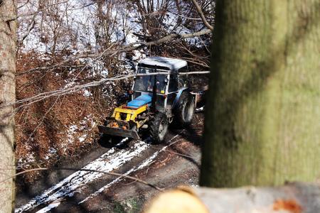 Un viejo tractor tirando de troncos de las montañas a la tierra para su próximo procesamiento en invierno. O para algo de tabla y así sucesivamente