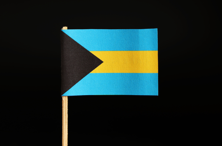 A official national Flag of the Bahamas on wooden stick on black background. The state located on north america. It was colony of united kingdom