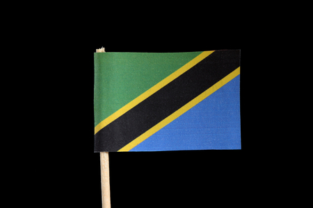A national official flag of Tanzania on toothpick on black background. A yellow edged black diagonal band. Upper triangle is green and the lower is blue. Stockfoto