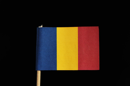 A national flag of Chad on toothpick on black background. A vertical tricolor of blue, gold and red