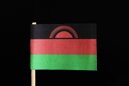A original  flag of Malawi on toothpick on black background. Consists of a horizontal triband of black, red and green. Charged with a red rising sun with 31 rays centred on the black stripe. Stock Photo
