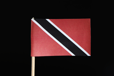 A official and original flag of Trinidad and Tobago on the toothpick on black background. A red field with a white edged black diagonal band from the upper hoist side to the lower fly side.