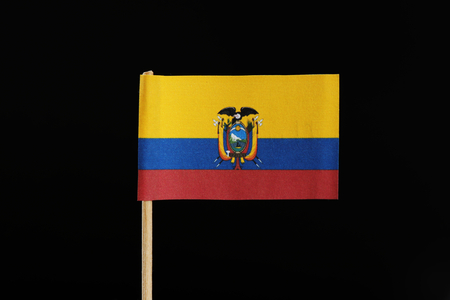 A national flag of Ecuador on toothpick on black background. A horizontal tricolor of yellow, blue and red with the national coat of arms at the center. Stock Photo