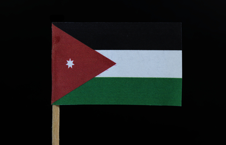 A official and unique flag of Jordan on toothpick on black background. A horizontal triband of black, white and green; with a red chevron based on the hoist side containing a white seven-pointed star.