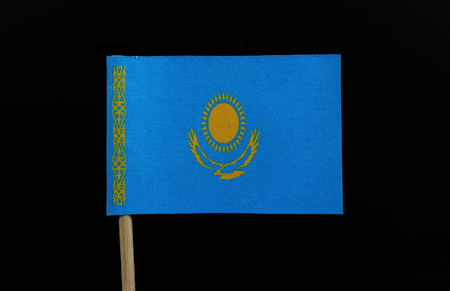 A unique flag of Kazakhstan on toothpick on black background. A gold sun with 32 rays above a soaring golden steppe eagle, both centered on a sky blue field. Stock Photo