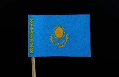 Eine einzigartige Flagge Kasachstans auf Zahnstocher auf schwarzem Hintergrund. Eine goldene Sonne mit 32 Strahlen über einem aufsteigenden goldenen Steppenadler, beide zentriert auf einem himmelblauen Feld. Standard-Bild