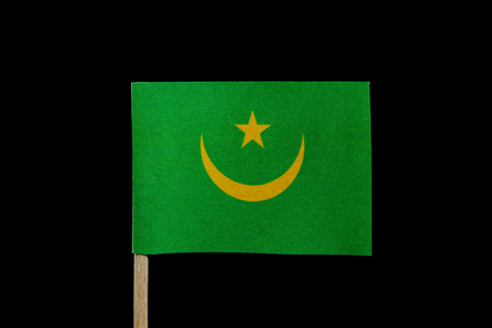 A official flag of Mauritania on toothpick on black background. Consists of a green field with a golden upward-pointed crescent and star.