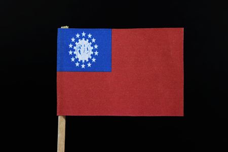 A old official flag of Myanmar on toothpick on black background. Flag of socialist republic of the union of Burma.
