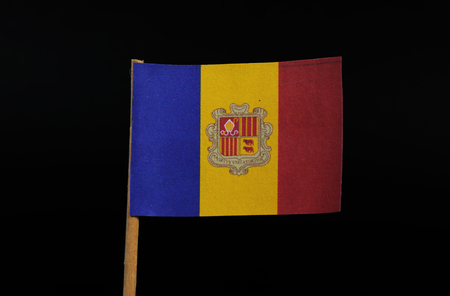 A official and national flag of the Principality of Andorra on toothpick on black background. A vertical tricolour of blue, yellow and red with the National Coat of Arms centred on the yellow band.
