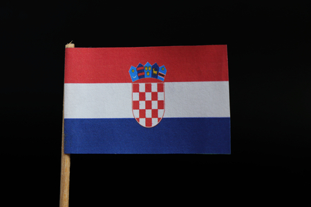 A official and unique flag of Croatia on toothpick on black background. A horizontal tricolour of red, white, and blue with the Coat of Arms of Croatia in the centre.