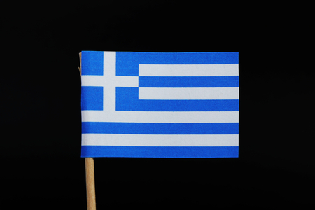 A official and national flag of Greece on toothpick on black background. Nine horizontal stripes, in turn blue and white a white cross on a blue square field in canton. Foto de archivo