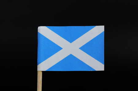 A unique flag of Scotland on toothpick on black background. A blue field with a white diagonal cross that extends to the corners of the flag. In Blazon, Azure, a saltire Argent.