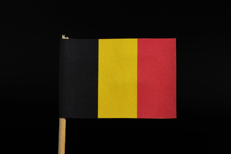 A beautiful, national flag of the kingdom of Belgium on toothpick on black background. A vertical tricolour of black, yellow, and red. Фото со стока