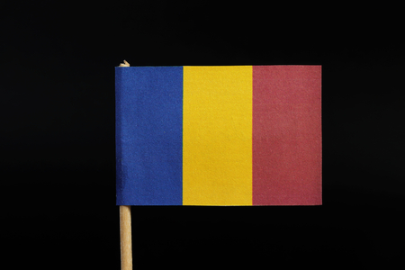 A national flag of Romania on toothpick on black background. A vertical tricolor of blue, yellow, and red.