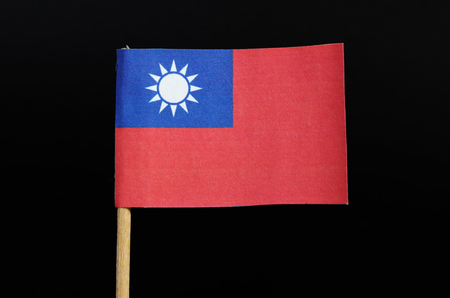 A national flag of Taiwan on toothpick on black background. A red field with a navy blue canton bearing a white sun with 12 triangular rays.