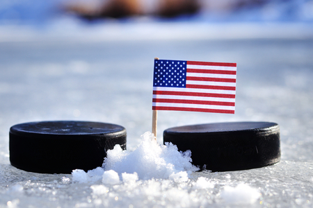 A American flag on toothpick between two hockey pucks.  A United States will playing on  cup in group A. 2019 IIHF World Championship in Slovakia.