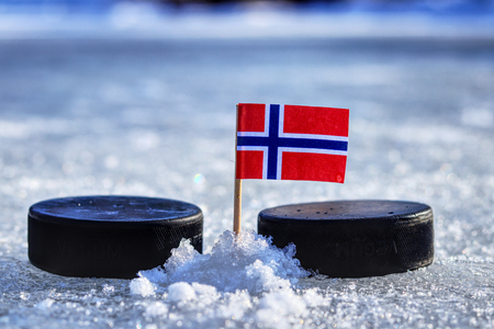 A Norwegian flag on toothpick between two hockey pucks on ice in outdoor. A Norway will playing on  cup in group B. 2019 IIHF World Championship in Slovakia.