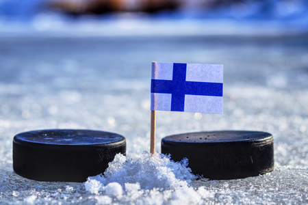 A finland flag on toothpick between two hockey pucks. A finland will playing on  cup in group A. 2019 IIHF World Championship in Slovakia 版權商用圖片