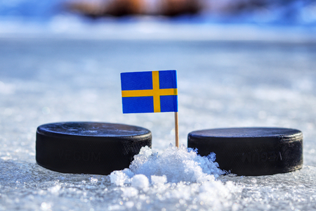A Sweden flag on toothpick between two hockey pucks.  A Sweden will playing on  cup in group B. 2019 IIHF World Championship in Slovakia