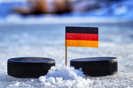 A Germany flag on toothpick between two hockey pucks.  A Germany will playing on  cup in group A. 2019 IIHF World Championship in Slovakia. 版權商用圖片
