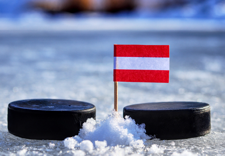 A Austrian flag on toothpick between two hockey pucks.  A Austria will playing on  cup in group B. 2019 IIHF World Championship in Slovakia.