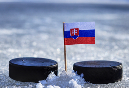 A slovakian flag on toothpick between two hockey pucks on ice in outdoor. A Slovakia host  cup and Slovakia playing in group A. 2019 IIHF World Championship in Slovakia.