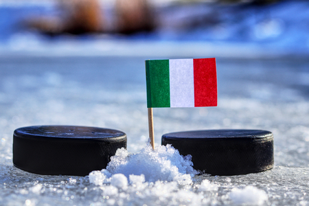A Italian flag on toothpick between two hockey pucks.  A Italy will playing on  cup in group B. 2019 IIHF World Championship in Slovakia.
