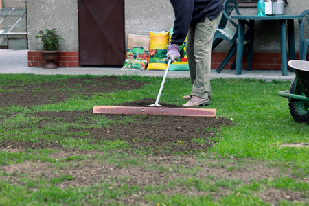 Important work after winter. Man add earth on garden and then aligning the surface with special tool. The tool is create from iron stick and wooden board. Summer landscaping in the garden.