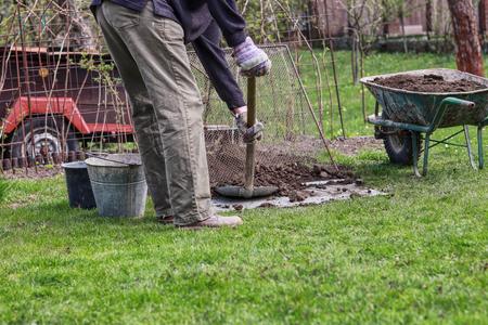 Summer worker is sifting soil through handmade sieve. Summer work. Landscaping the garden. Wheelbarrow full of clean earth. Manual hard work on garden. Regrouping earth