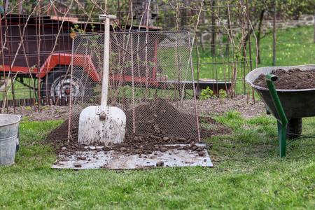 Working garden tools. Propped shovel against the sieve. Wheelbarrow full of earth. Bucket hidden in corner. Important utensils for labour on the garden. Summer work.