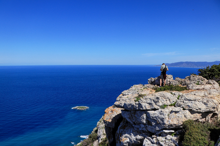 Back view of freedom man stand on rock cliff looking at blue sea and Cypriot nature. Contrast between midget and infinitely water land. Rock hill in Akamas peninsula national park with athlete.