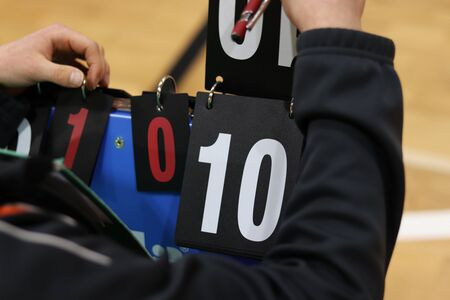 Young boy turns number on abacus in a volleyball match. Determining the score. Tournament recorder. Number Ten. Scorekeeper. Important person in a every tournament. Homemade scoreboard