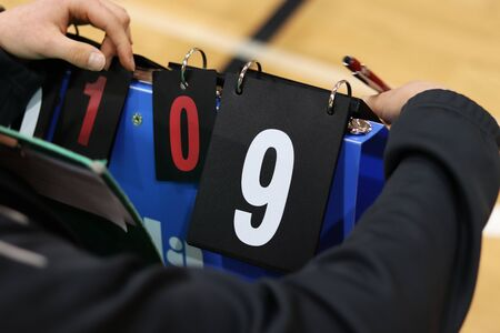 Scorekeeper keep attention during volleyball match not to forget turns numbers. White number nine on black background. Sport abacus. Indoor sport. Summer brigade.