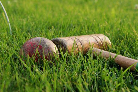 Sport equipments in green grass. Red ball, goal, cricket stick. Main sport in England Stok Fotoğraf