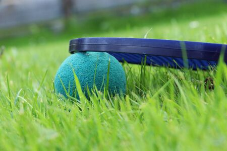 A look at the past, the times when we were children. Detail on softenis ball and racket. Best game in childhood. Toys forgotten in the grass.