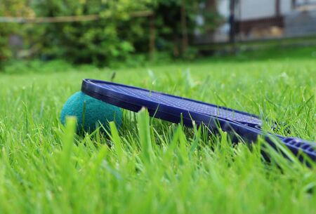Plastic softtenis racket hidden in grass after magical game between two boys. Detail for green and blue special ball and black ultra lightweight racket for every child.