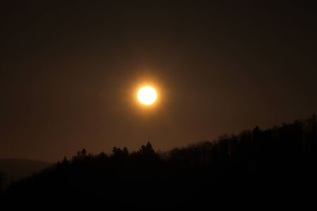 Beautiful orange ball on dark sky with shadows of trees. Sunset over black mountain. Eclipse of the sun in real time.