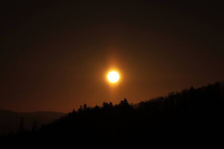 Orange and yellow circle with shining to surroundings. Sun over black mountain with shadows of trees. Orange blaze on the sky.