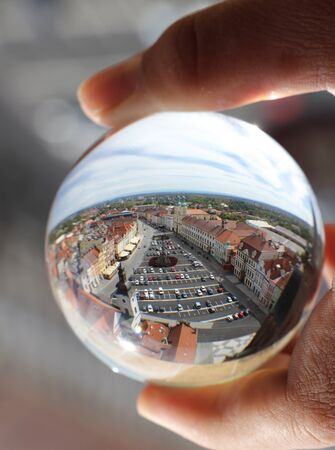 Market square of Hradec Kralove in lens ball which photographer is holding in fingers. Crystal ball wih recletion of Hradec Kralove in morning.