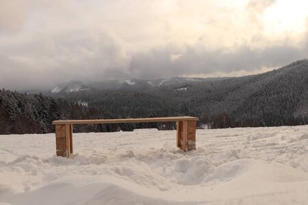 Wonderful winter atmosphere on Beskydy mountains. Wooden homemade bench settled in a snow cover. White and grey huge clouds rolling through the mountains.