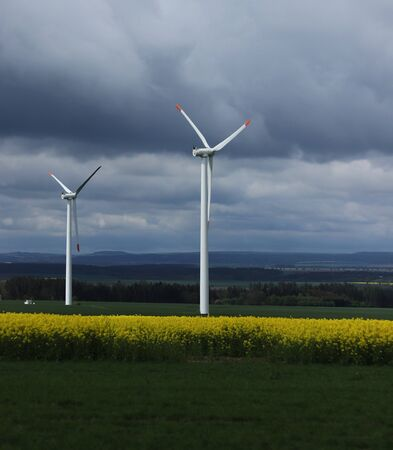 Field of oilseed rape and wind power station in czech republic. Rapeseed is everywhere. Ecological electric power. Replacement for coal-fired power station. Stok Fotoğraf